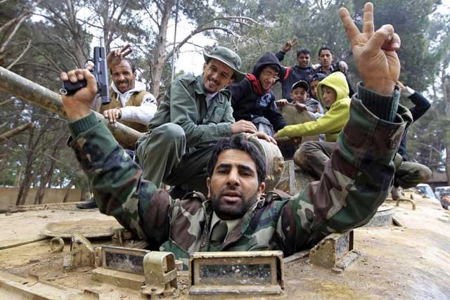 Ciudadanos libios, en un blindado, celebran su triunfo frente a las fuerzas de Gadafi en el este del país. | Reuters