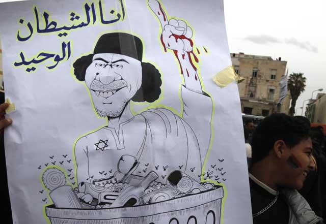 Un ciudadano de Bengasi muestra un dibujo despectivo de Muamar Gadafi. | Reuters