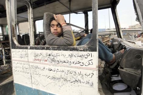 Un adolescente egipcio en el interior de un microbús calcinado en El Cairo.| Khaled Elfiqi