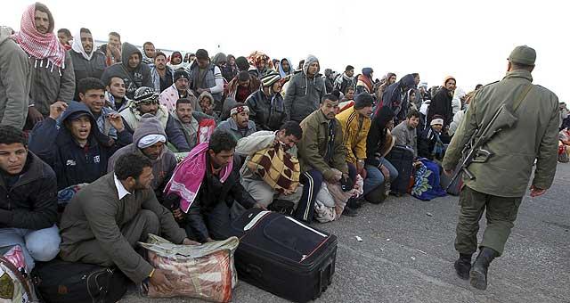 Ciudadanos egipcios residentes en Libia esperan junto a sus pertenencias en el paso tunecino de Ras Ajdir.   Efe