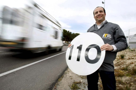 Un empresario de láminas para la señalización, sostiene una con la nueva velocidad. | Efe