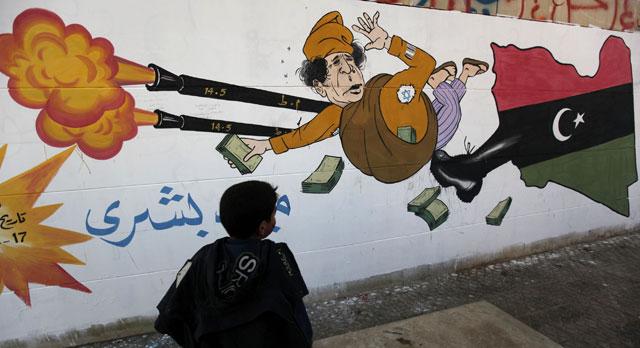 Un niño observa un grafiti sobre Gadafi en Bengasi (Libia).   Ap