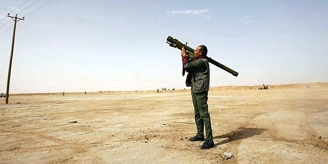 Un rebelde libio apunta con lanzaproyectiles en busca de los aviones de Gadafi.   Reuters