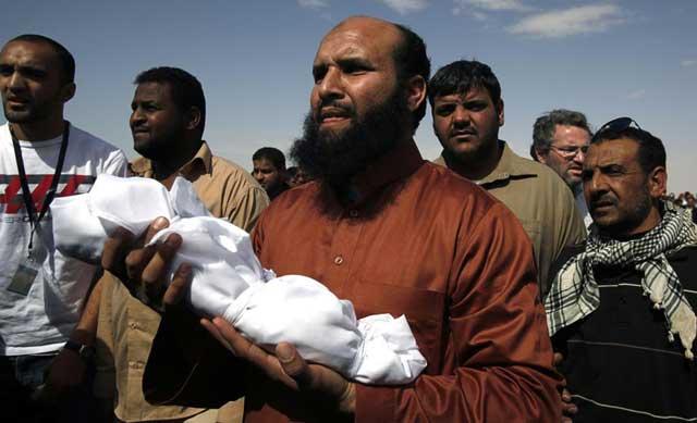 Un hombre sostiene el cadáver de un bebé fallecido en los combates en Brega. | Reuters