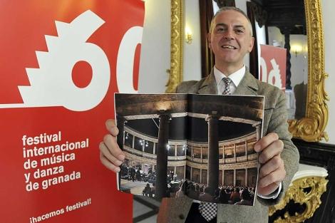 El director del Festival de Granada mostrando una foto de la pasada edición. | Efe