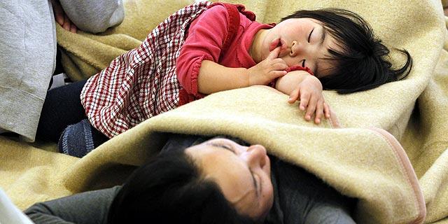 Una niña duerme con su madre en un refugio. | Reuters