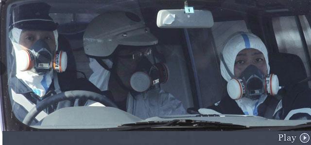 Oficiales de policía patrullan con máscaras de gas en el área de la planta nuclear. | AP