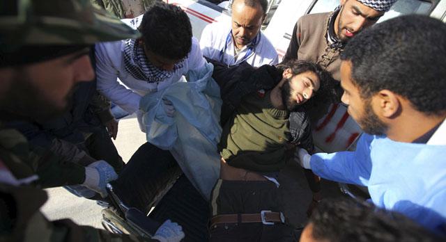 Médicos atienden a un rebelde herido en Brega.   Efe