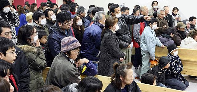 Habitantes de Fukushima evacuados por los problemas de la central nuclear observan las noticias desde su refugio. | Afp