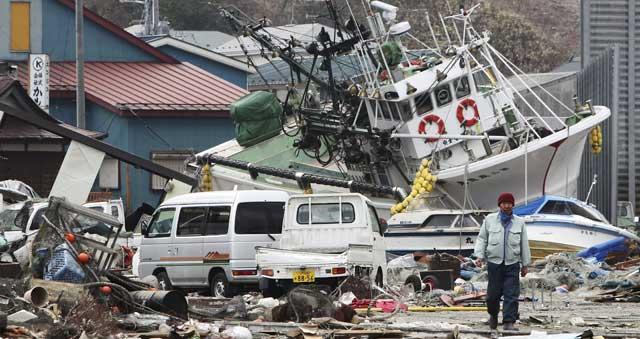 Un pescador comprueba los daños en el puerto de Hachinoche. | Efe