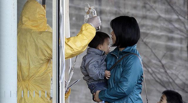 Un experto mide la radiación de una madre y su hijo. | Reuters