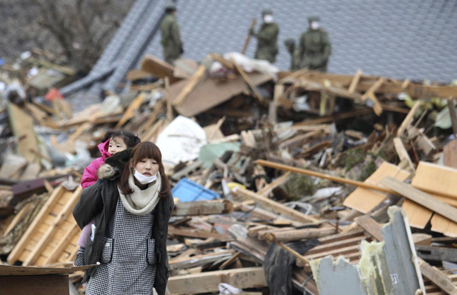 Una mujer con una niña camina por la ciudad devastada de Ufanato, al norte del país. | AP