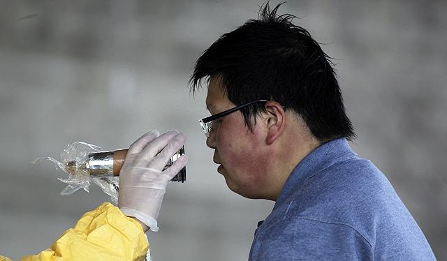Un miembro del Ejército mide la radiación de un vecino de Fukushima. | Reuters
