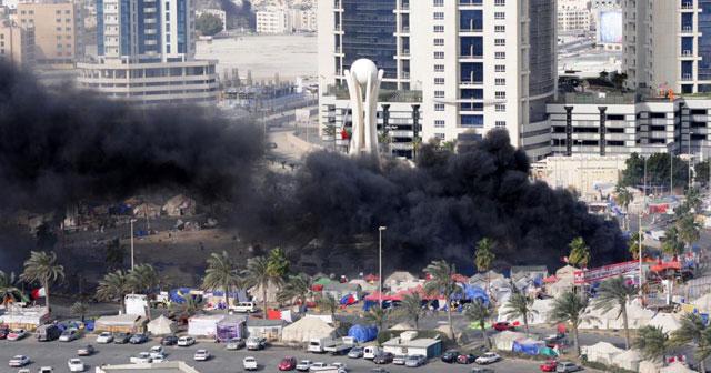 Una intensa columna de humo negro sale de la Plaza de la Perla, en Manama, tras el asalto policial. | Afp