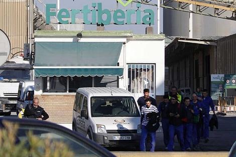 Operarios del polo industrial de Huelva saliendo de una factoría química.   Elisabeth Domínguez