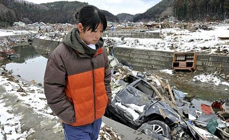 Una joven que logró sobrevivir al terremoto, camina por la arrasada ciudad de Minamisanriku, en Miyagi. | Efe
