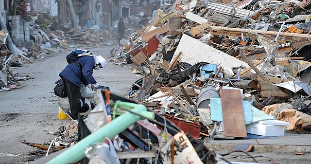 Un hombre busca entre los escombros de una casa. | Afp