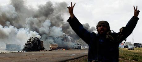 Un rebelde libio ante vehículos de Gadafi destruidos en un ataque aéreo.   Reuters