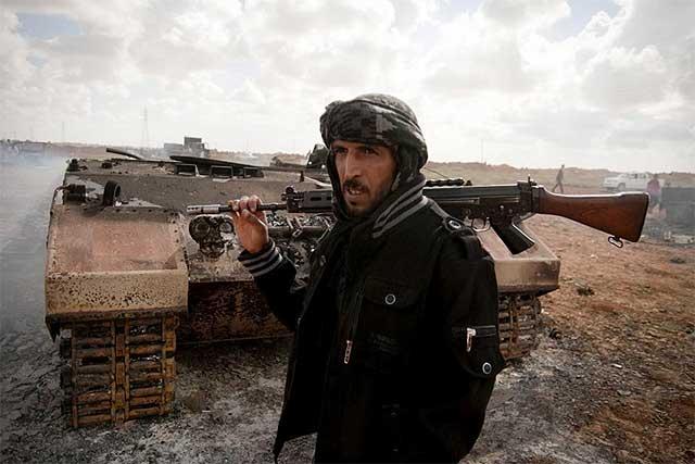 Un miliciano, junto a los restos de carros blindados derribados por Francia.| Efe