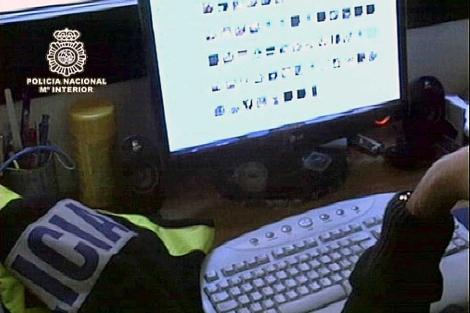 Un agente estudia material intervenido en una operación contra la pederastia.   Interior