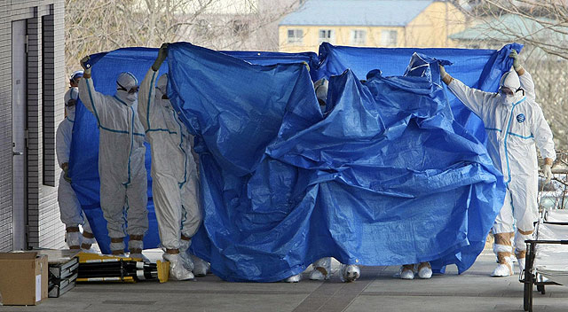 Miembros de seguridad protegidos preparan el transporte de los afectados. | AP