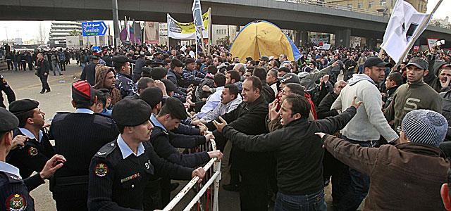 La policía intenta desmontar el campamento organizado por los jóvenes en una plaza de Ammán. | Reuters