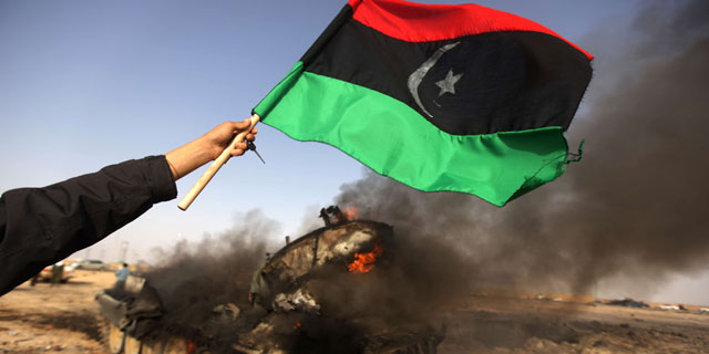 Un rebelde libio sostiene una bandera anterior al régimen de Gadafi frente a un tanque ardiendo. | Afp