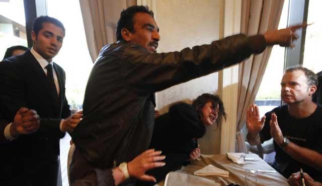 Un miembro de las fuerzas de seguridad de Gadafi detiene a Eman Al Obaidi, en Bengasi. | Reuters