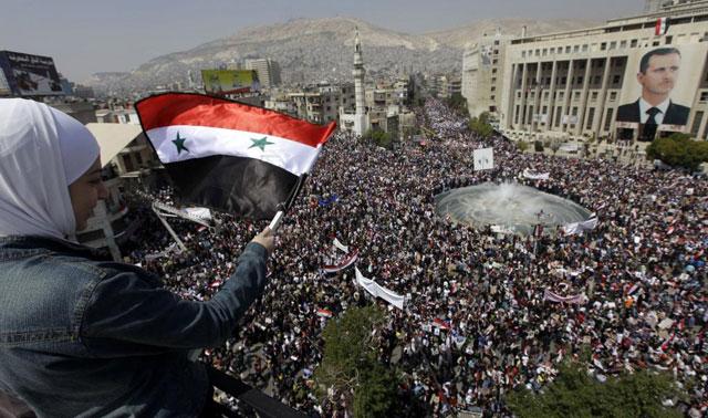 Una simpatizante del presidente agita la enseña nacional en la multitudinaria manifestación a favor de Asad en Damasco. | Ap