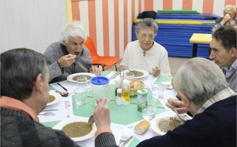 Algunos de los usuarios del comedor conversan durante la comida. | Domènec Umbert