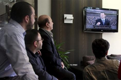 Ciudadanos sirios siguen por televisión el discurso de ayer de Assad. | Efe