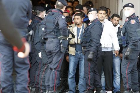 Inmigrantes bajo vigilancia en el puerto de Lampedusa (Italia). | Afp