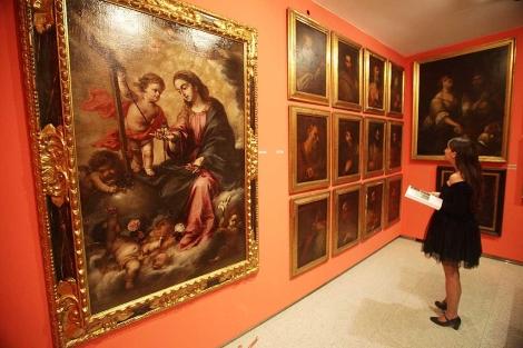 Una joven observa el catálogo, ante el lienzo de Valdés Leal.   Fernando Ruso