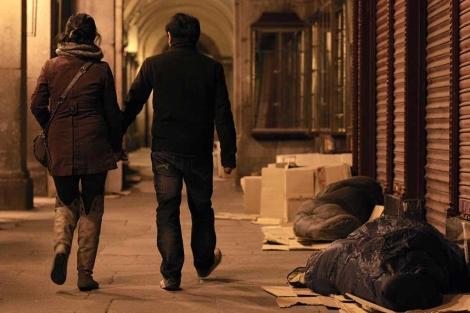 Viandantes pasan al lado de dos personas durmiendo en la calle. | A. Heredia