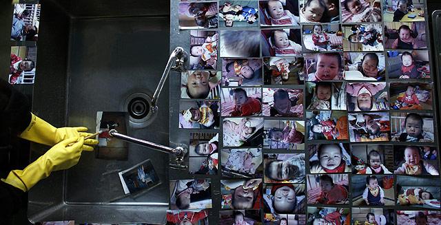 Una voluntaria limpia fotografías encontradas entre los escombros. | Reuters