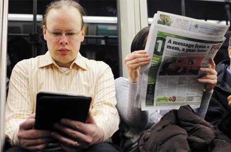 Un lector de libro electrónico junto a otro de papel. | Reuters