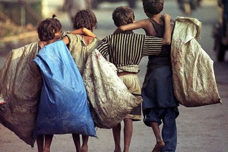 Varios niños indios caminan por una calle de Calcuta tras un día de trabajo.