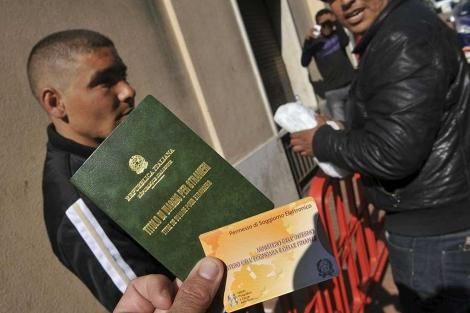 Un grupo de emigrantes muestra el permiso de residencia italiano.| Efe