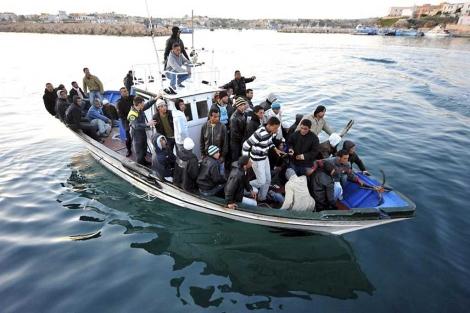 Inmigrantes tunecinos llegan en un bote a la isla italiana de Lampedusa.| Efe