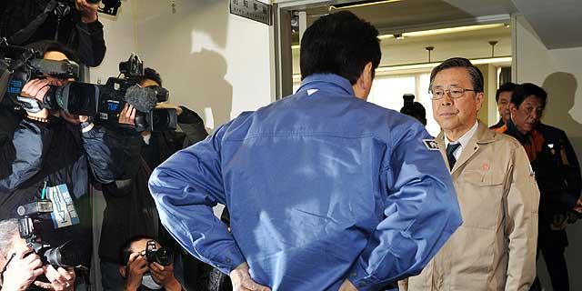 El primer ministro japonés, Naoto Kan (de azul) es recibido por el gobernador de la prefectura de Fukushima, Yuhei Sato.   ap