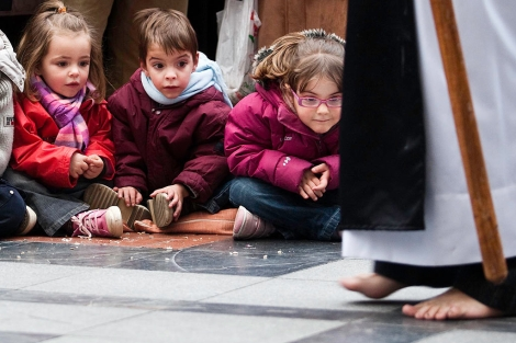 La fotogtafía ganadora, tres niños sorprendidos ante los pies descalzos de un cofrade. | P. R.