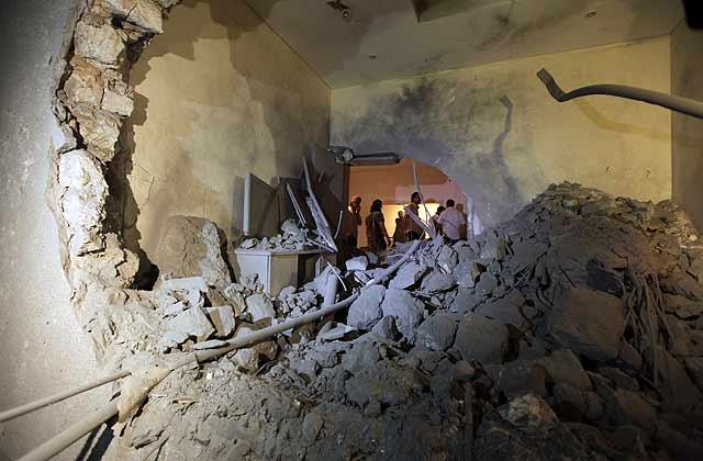 Inspeccionan el estado en que ha quedado la casa del hijo de Gadafi. | Afp
