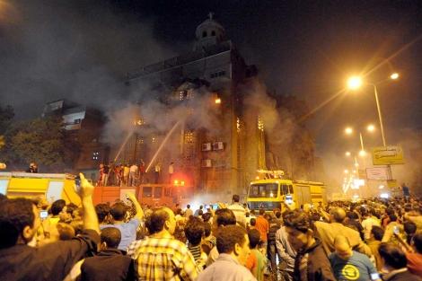 Los bomberos intentan apagar el fuego provocado en la iglesia copta Mar Mina. | Afp