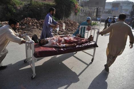 Sanitarios y personas voluntarias trasladan a un herido por el atentado. | Afp MAS IMAGENES
