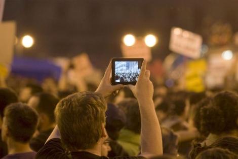 Un joven graba la concentración en Madrid.|EFE