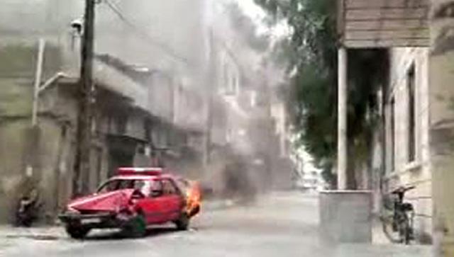 Un coche de la policía arde durante las protestas en la ciudad de Homs. | Reuters