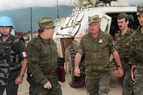Una mujer ante una pintada con la imagen de Mladic en Belgrado. | Reuters