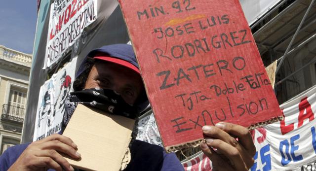 Uno de los asistentes a Sol muestra una tarjeta roja a Zapatero.   Efe