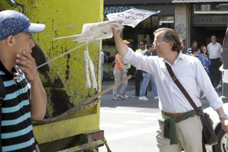 El hombre tirando varios carteles a la basura.   Efe