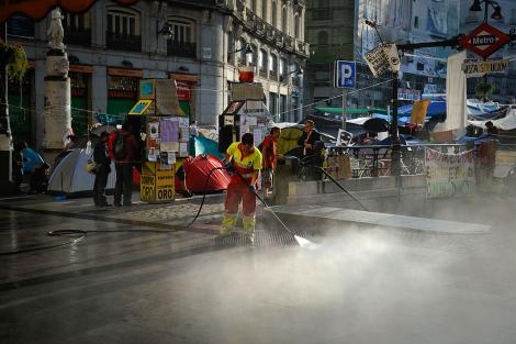 Labores de limpieza en Sol, donde los 'indignados' llevan dos semanas acampados. | AFP